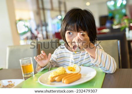 Asian girl eating breakfast  - stock photo