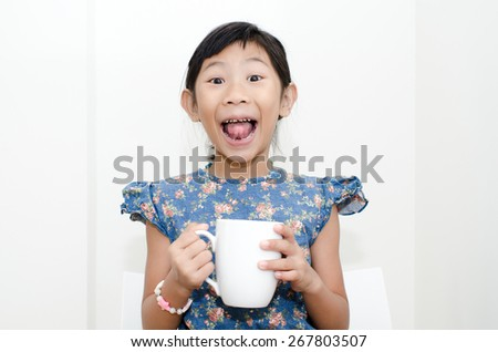 Asian girl holding a cup of milk during breakfast at home. - stock photo