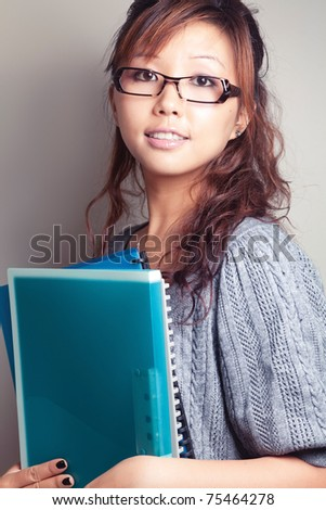 Asian girl holding a textbook. Wear glasses. - stock photo