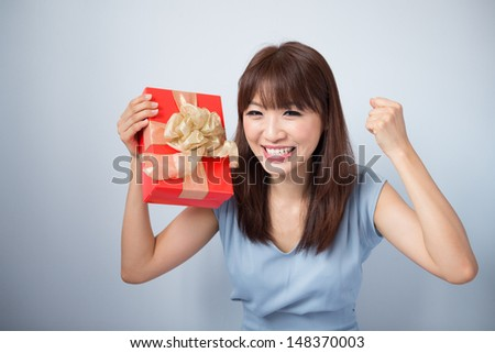 Asian Girl Holding Gift Box and Smiling happily, cute Asian beauty model, isolated on blue background - stock photo