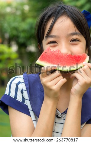 Asian girl holding slice of watermelon - stock photo