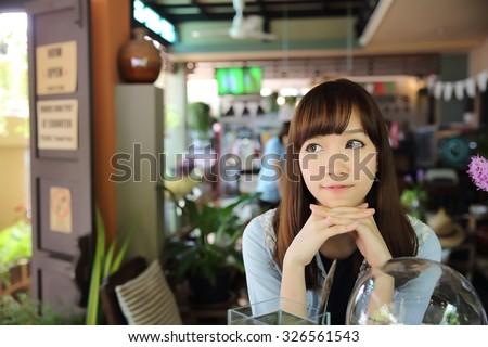 Asian girl in coffee shop - stock photo