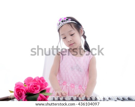 Asian girl in princess dress playing keyboard on white. - stock photo