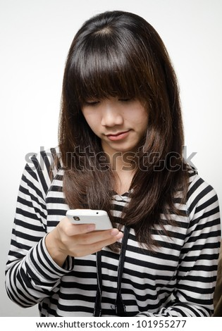 Asian girl is checking her smartphone - stock photo