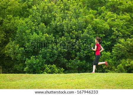 Asian girl jogging at outdoor park - stock photo