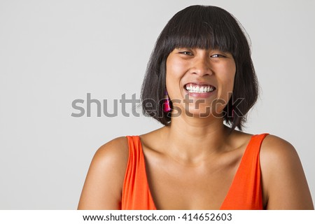 Asian girl laughing hard against a white background - stock photo