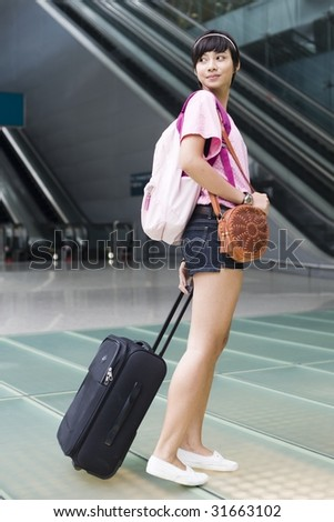 asian girl leaving singapore's changi airport terminal and turning her head back - stock photo