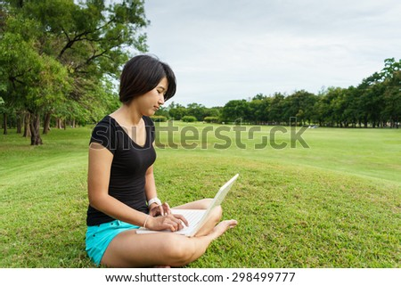 Asian girl look at her laptop while she sit on green grass in the garden - stock photo