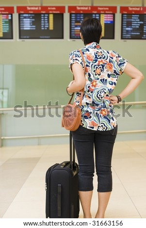 asian girl looking at departing flight on the monitor screens at singapore's changi airport terminal - stock photo