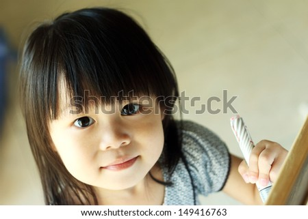 Asian girl looking up at camera while writing on board with pen in hand - stock photo