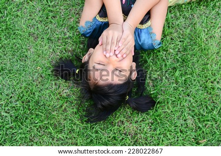 Asian girl lying on grass and closed her mouth, vertical. - stock photo