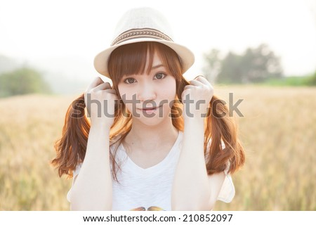Asian girl on meadow  - stock photo
