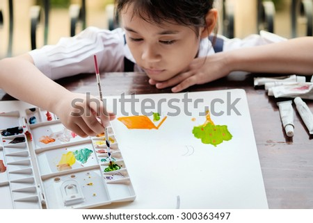 Asian girl painting brush watercolors on paper. - stock photo