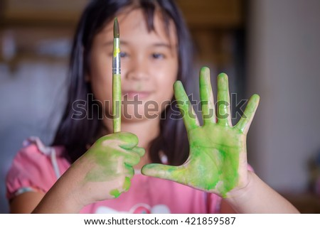 Asian girl painting in classroom. - stock photo