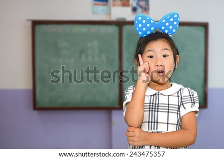 Asian girl pointing in the classroom - stock photo