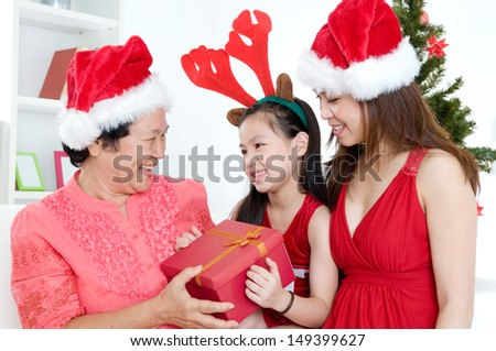 Asian girl presenting christmas gift to grandmother - stock photo