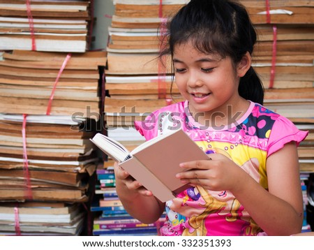 Asian girl reading a book on an old books background - stock photo