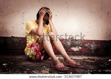 asian girl  sad alone sitting  near old wall cement,vintage tone - stock photo