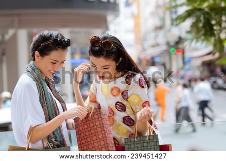 Asian girl showing something in the shopping bag to her friend - stock photo