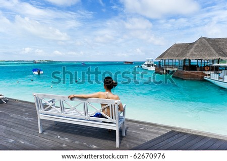 asian girl sitting in chair watching the sea on the deck - stock photo