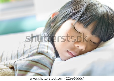 Asian girl sleeping on bed covered with blanket. - stock photo