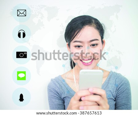 Asian girl smiling so happy using a blur smart phone with modern technology and digital layer effect with icons over blur World map  . business strategy concept. (Selective focus) - stock photo