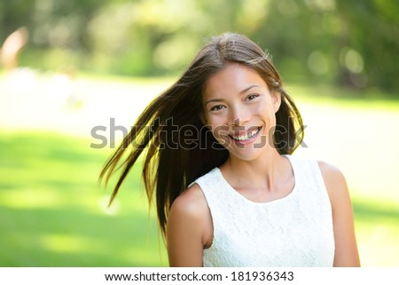 Asian girl spring portrait in park. Smiling happy mixed race Asian Caucasian woman in 20s looking at camera. - stock photo