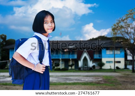 asian girl student wear uniform Thai gesturing in front of the school building - stock photo