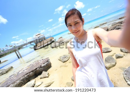 Asian girl taking selfie photo on the beach. - stock photo