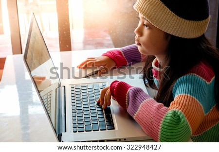 Asian Girl using a laptop. - stock photo