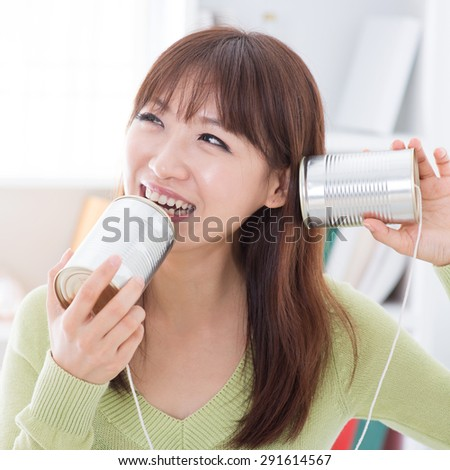Asian girl using old technology, talk and listen to communication cans. Young woman indoors living lifestyle at home. - stock photo