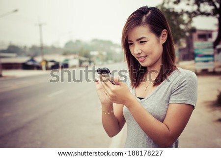 asian girl using smartphone happy on the road in thailand, process color, process color - stock photo