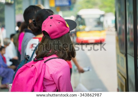 Asian girl waiting for bus at station - stock photo