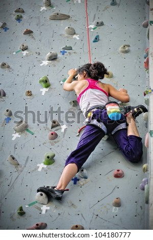 Asian girl wearing harness and belaying rope, climbing on a very high rock climbing wall. - stock photo