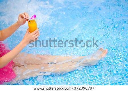 Asian girl with a cocktail at swimming pool - stock photo
