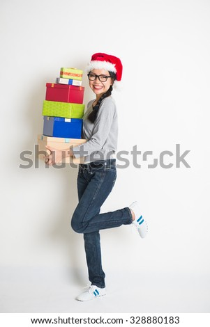 asian girl with christmas gift and santa hat - stock photo