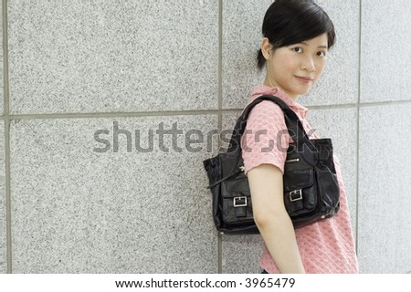 asian girl with handbag outdoors - stock photo