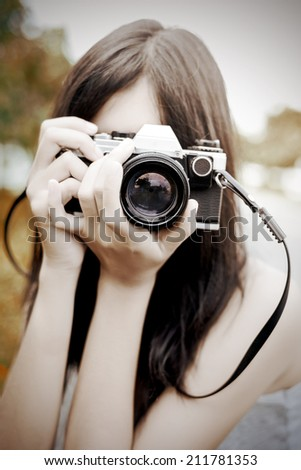 asian girl with vintage photo camera on background - stock photo