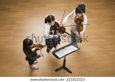 Asian girls playing violins - stock photo