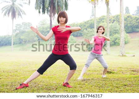 Asian girls practicing tai chi in the outdoor park - stock photo