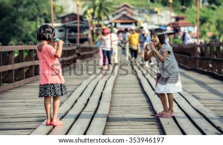 Asian girls talking on a can phone - stock photo