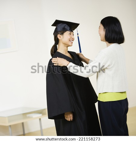Asian graduate smiling at mother - stock photo