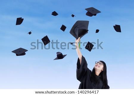 Asian graduate throw graduation cap under blue sky - stock photo