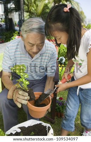 Asian grandfather with his granddaughter working in the garden - stock photo