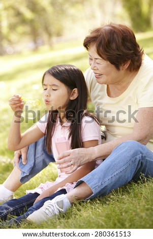 Asian grandmother and granddaughter blowing bubbles in park - stock photo