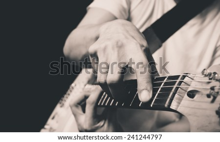 asian guitarist / musician plays electric guitar, isolated on black & old black and white film processed - stock photo