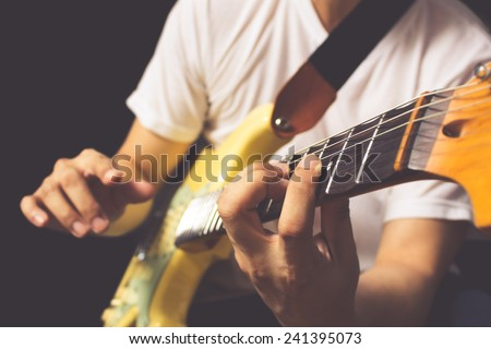 asian guitarist / musician plays electric guitar, isolated on black & old color film processed - stock photo