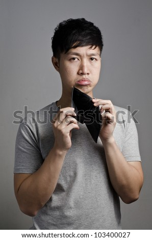 Asian guy look at his empty wallet on gray background - stock photo