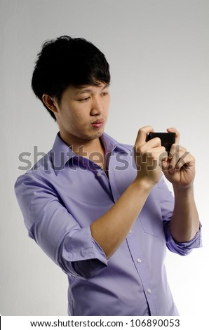 Asian guy take a photo with his smart phone - stock photo