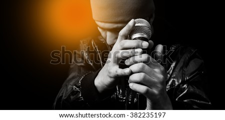 asian handsome singer holding dynamic microphone. isolated on black - stock photo